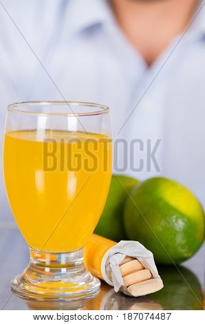 Lemon, pills of vitamin C and a glass of vitamin C dissolved over the table.