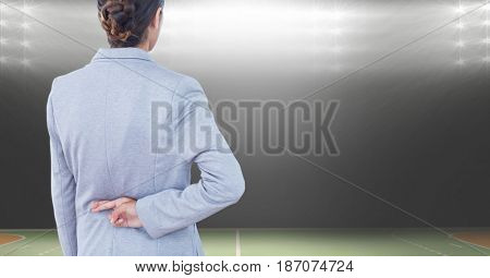 Digital composite of Rear view of businesswoman crossing fingers at stadium