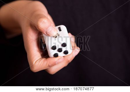 Quito, Ecuador - February 10, 2017: Man holding a Fidget Cube stress reliever, Fingers Toy.