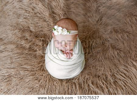 Little baby girl wrapped in white blanket with flowery hairband, sitting on brown furry pillow