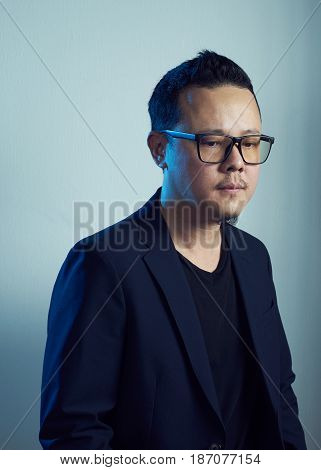 Portrait of asian Hesitant young man in blank black suit .