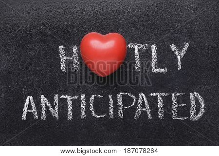 hotly anticipated heart phrase handwritten on blackboard with heart symbol instead of O