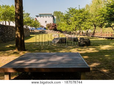 Wooden picnic table in a public park shaded by trees with a wooden walkway in the right side of the frame and a stone wall on left of the frame.