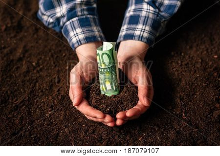 Hands with fertile soil and euro money banknotes female farmer handful of cultivated land that makes profit and steady income from sustainable agricultural activity like organic growth of crops