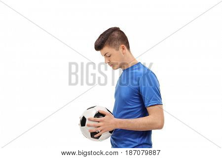 Profile shot of a sad teenage soccer player holding a football isolated on white background