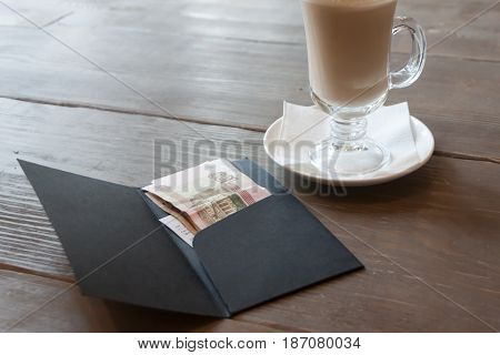 The Cover For Money Lying On A Little Table In Cafe