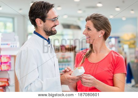 Pregnant woman shopping in drug store being advised by sales man