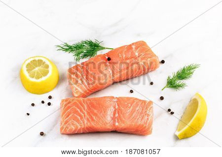 A photo of two slices of salmon on a white background with a place for text, with slices of lemon, salt and pepper, and dill sprigs