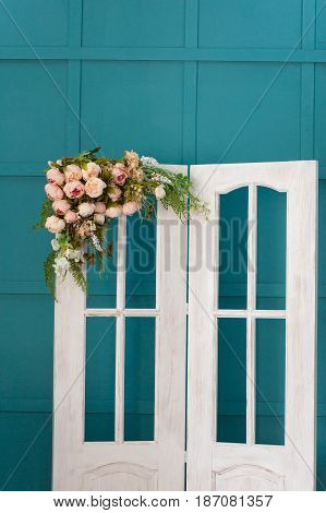 Wedding arch in the form of a white door with flowers on a turquoise background