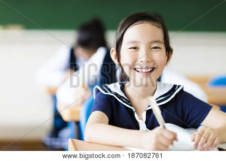 smiling little girl in classroom and her friends