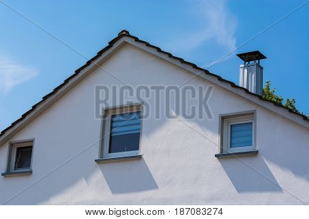 Gable side of a multi-family house of the 60s after modernization against blue sky.