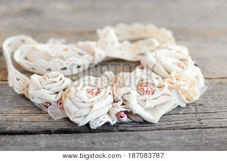 Recycled fabric necklace from lace trims, beads and felt base isolated on a vintage wooden background. Summer beaded fabric necklace for women and girls. Textile flowers art
