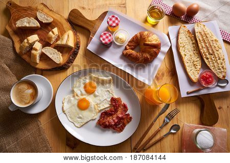 Continental breakfast croissant eggs bacon bread slices orange jiuce