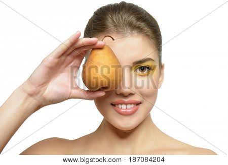 Young attractive girl posing at studio with ripe pear. Beautiful female face with healthy skin and art makeup. Health care, cosmetology, antiaging, beauty treatment, diet, feminity, spa concept.