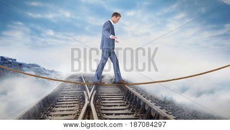 Digital composite of Digital composite image of businessman walking on rope over railway tracks