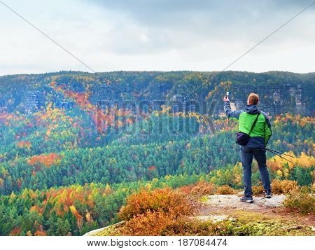 Ginger Hair Man Takes Photos With Smart Phone On Peak. Colorful Autumnal Landscape