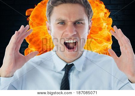 Digital composite of Close-up of angry businessman shouting against fire