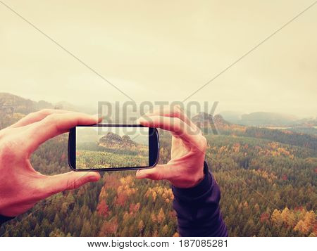 Man takes photos with phone on rock empire. Dreamy fogy mountains spring orange pink misty sunrise in a beautiful valley of rocky mountains.