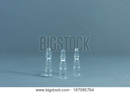 Medical ampoules, tablets and syringes on a dark background.
