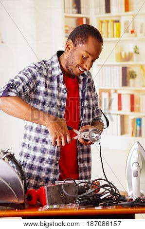 Happy Young African Ecuadorian male Technician repairing a machine using a Pliers.