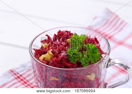 cup of fresh beetroot spread with walnuts on checkered dishtowel - close up