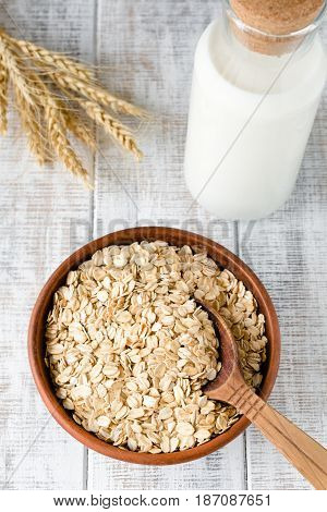 Oat flakes, rolled oats in bowl and bottle of milk on rustic wooden table. Top view