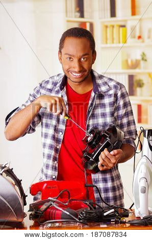 Happy Young African Ecuadorian smiling male Technician repairing a toaster with a screwdriver.
