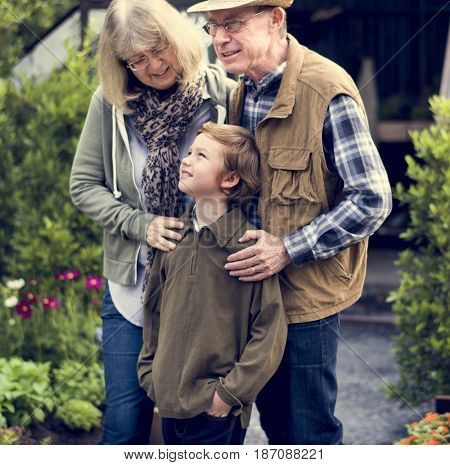 Senior couple with little boy gardening at home backyard