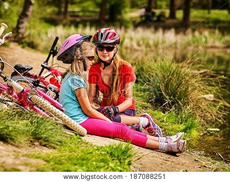 Bikes cycling children. Girl rides bicycle. Kids have rest near water in park. Bicycles are on coast. Rest on vacation on nature.