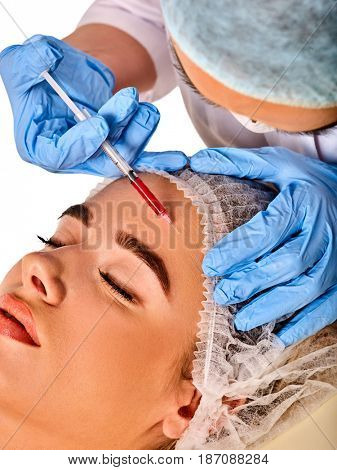 Filler injection for female forehead face. Plastic aesthetic facial surgery by doctor in beauty clinic. Beauty woman giving njections. Doctor in medical gloves with syringe. Wrinkle removal.