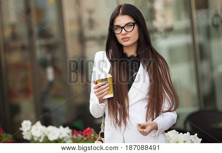 Cheerful fashionable blonde girl holding coffee cup outdoors in city street. woman in the street drinking morning coffee. Coffee on the go. Beautiful young woman while walking.
