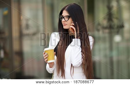 Cheerful fashionable brunette girl holding coffee cup outdoors in city street. woman in the street drinking morning coffee. Coffee on the go. Beautiful young woman while walking. Woman talks on Phone.