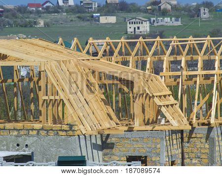 Wooden skeleton of the roof of the house under construction