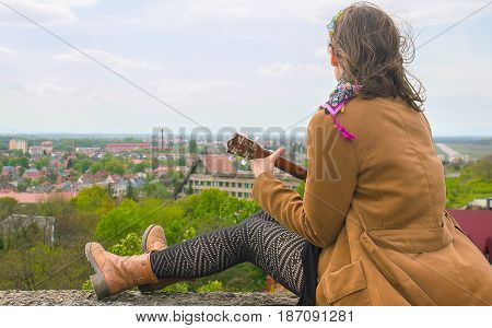 Young woman playing on Ukulele in the roof