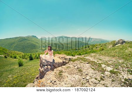 Young Beautiful Woman In White Dress Playing Flute Sitting On A Mountain Rock