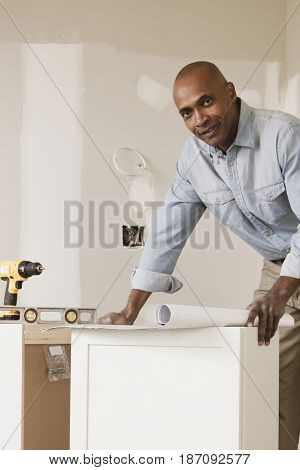African American man looking at blueprints in unfinished room