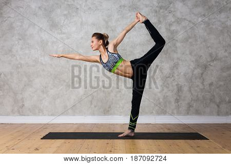 Young Woman Practicing Yoga Lord Of The Dance, Natarajasana Against Texturized Wall / Urban Backgrou