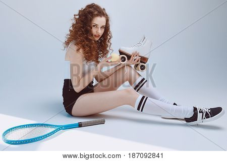 Attractive Stylish Hipster Girl Sitting And Holding Tennis Ball And Roller Skate