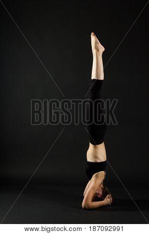 Sporty Beautiful Young Female Doing Yoga Supported Headstand /.salamba Sirsasana On Dark Black Backg