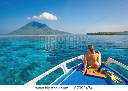 Young woman in swimsuit sit on boat at sunny day looking to a clean sea and volcano Manado Tua. North Sulawesi Indonesia.