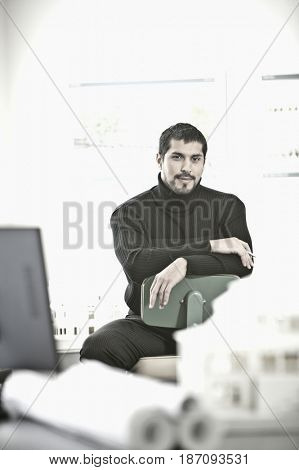 Smiling businessman sitting architect's in office