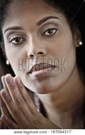 Serious woman with hands clasped