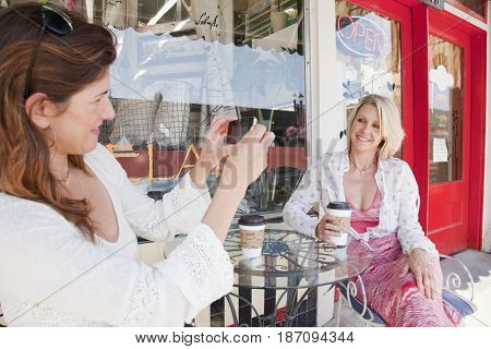 Caucasian woman drinking coffee and taking photographs in outdoor cafe