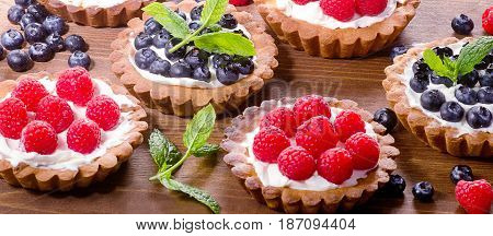 Homemade Tarts With Fresh Raspberries And Blueberries On A Wooden Background