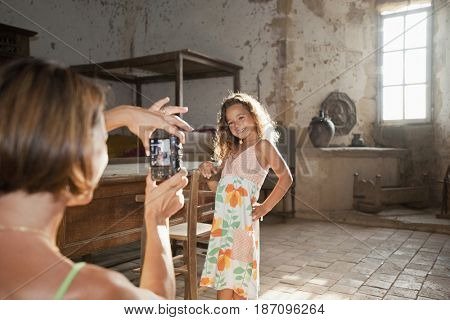 Mother taking photograph of daughter