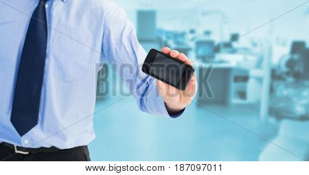 Digital composite of Midsection of businessman showing blank screen on mobile phone