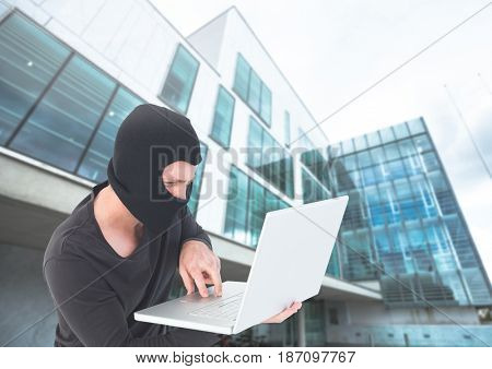 Digital composite of Criminal Man in balaclava on laptop in front of glass building