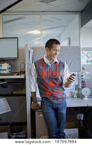 Mixed race businessman using cell phone in office cubicle