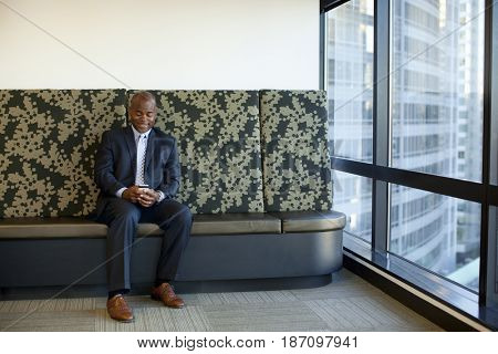 African American businessman using cell phone in office lobby