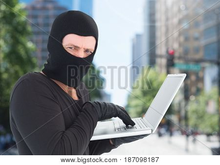 Digital composite of Criminal Man in balaclava on laptop in front of city